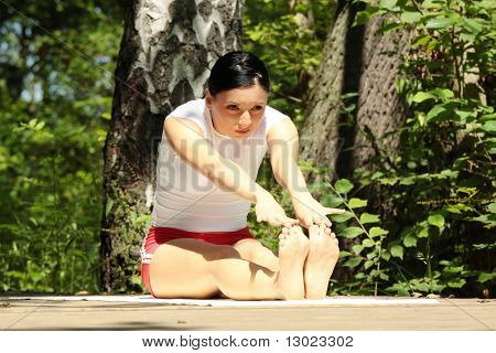 An attractive caucasian woman practicing yoga outdoors