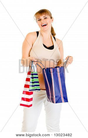 Happy pregnant woman holding shopping bags in hands isolated on white