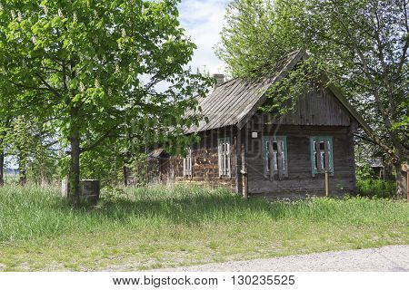 Old abandoned farmhouse near the blooming and blossoming trees against the bright spring sky - life goes on. «If time exists in nature, then it is not already open ...». (Konstantin Tsiolkovsky).