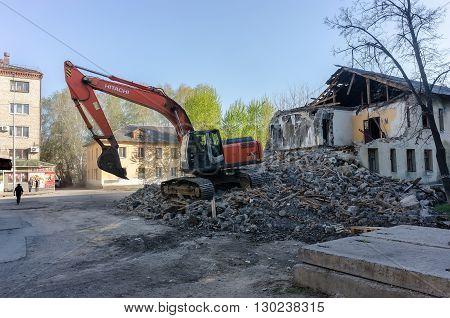 Tyumen, Russia - April 29, 2016: Excavator demolishing barracks for new construction project. Kievskaya street 70