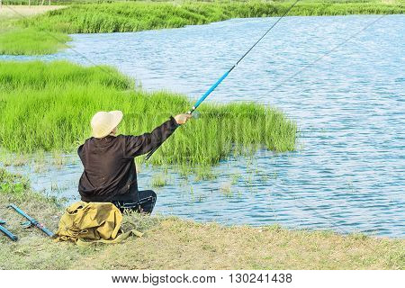 Fisherwoman in a white hat and a black tracksuit throws a fishing rod into the river