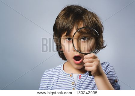 Child See Through Magnifying Glass, Kid Eye Looking with Magnifier Lens over Gray.