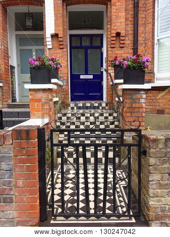 LONDON - MAY 18: Smart house entrance with blue front door and chequered tiles on May 18, 2016 in Hampstead, London, UK.