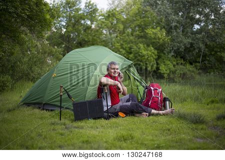 A Man Sitting Near Tent And Talking On The Phone.