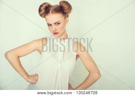 Close-up portrait of offended beautiful girl with funny hairstyle looking at camera.