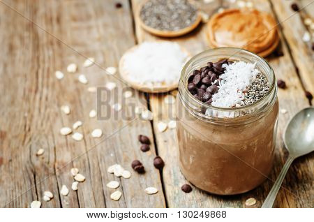 Chocolate Coconut Chia seeds overnight oats on a dark wooden background.