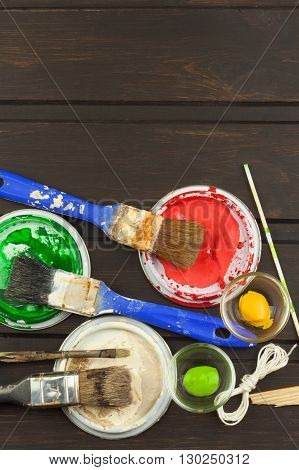 Brushes and paint on a wooden table. Painter tools. Workshop painter. Needs painting. Sales painting needs. Clutter on the workbench. Sales of color. Advertising on painting.