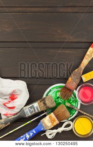 Brushes and paint on a wooden table. Painter tools. Workshop painter. Needs painting. Sales painting needs. Clutter on the workbench. Sales of color. Advertising on painting. poster