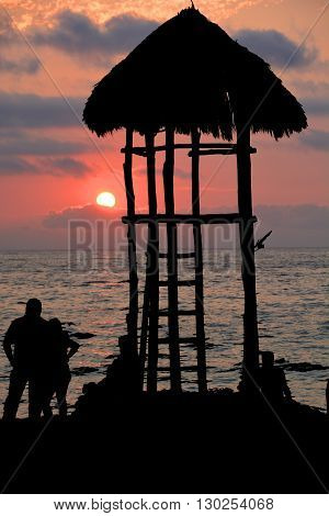 Silhouette of a lifeguard tower on Los Muertos beach against sunset sky. Puerto Vallarta, Mexico