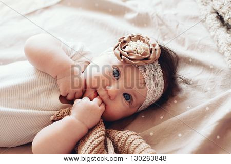 Portrait of a 4 month cute baby girl wearing lace flower headband and lying down on a bed with polka dot brown bedding