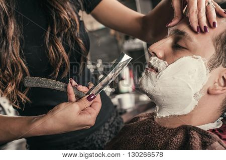 Female barber shaving a client's beard in a barber shop poster
