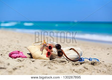 family vacation concept - beach bag, suncream, sandals on sand beach