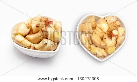 Fresh ginger  in a heart shaped bowl, isolated on white