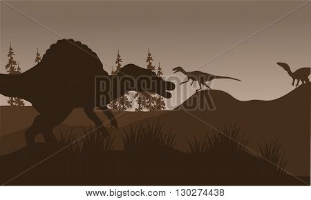 Silhouete of spinosaurus and eoraptor in hills with brown backgrounds