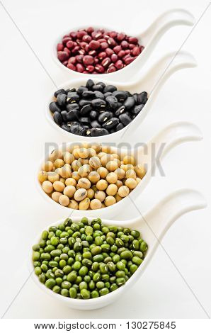 Set of beans Soy or yellow bean Azuki or red bean Mung bean and black bean in white spoon on white background.