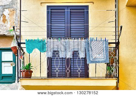 Italian Balcony in Palermo with Closed Wooden Shutters Decorated with Mats