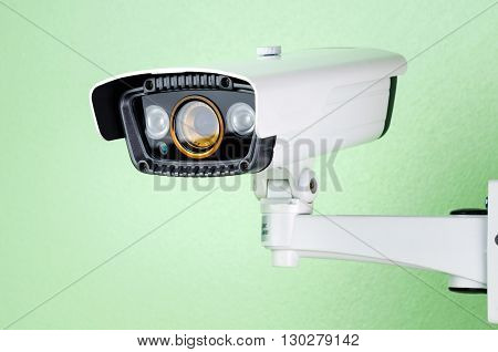 white CCTV security camera on green wall.