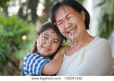 Happy little Asian girl hugging her grandmother