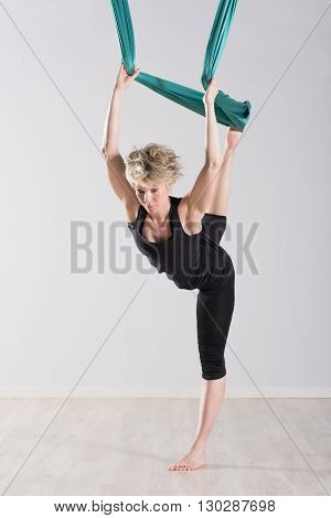 Woman Stretching Legs Back With Green Tarp