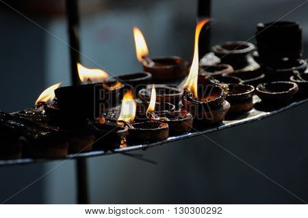 Burning candle row in a hindu temple Orissa India