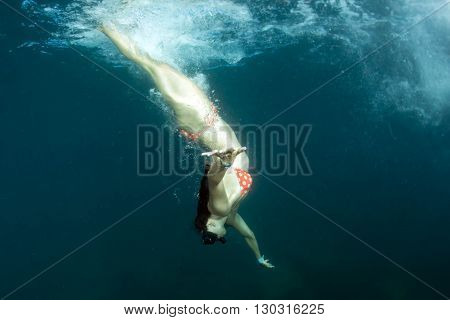 beautiful bikini girl diving in the deep blue sea