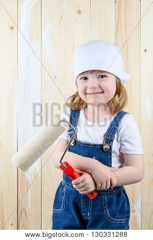 Little Girl Paints A Wooden Wall