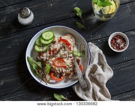 Rice with meat and sweet red pepper. Healthy delicious lunch. On a dark wooden background