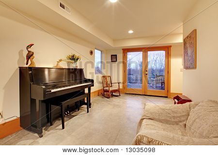 Room With Black Piano And Large Door In The Evening