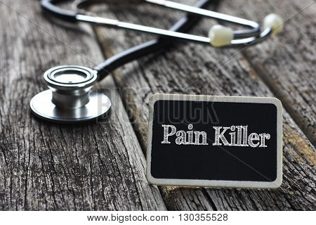 Medical Concept-Pain Killer word written on blackboard with Stethoscope on wood background
