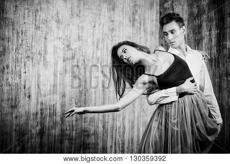 Beautiful young couple in love dancing tango with passion. Professional dancers. Latino dancers. Toned photo, sepia. Retro style.