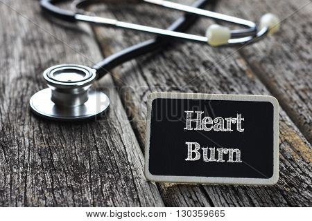 Medical Concept- Heart Burn word written on blackboard with Stethoscope on wood background