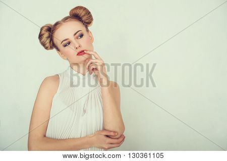 Close-up portrait of thoughtful beautiful girl with funny hairstyle. Sly and scheming young woman face expression.