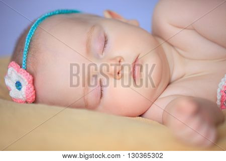 Adorable little girl slipping in her bed . Close-up