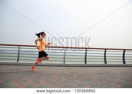 one asian woman runner running on seaside