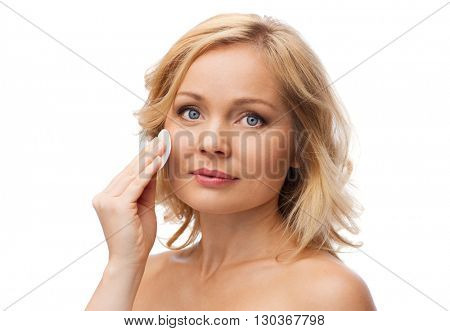 beauty, people and skincare concept - young woman cleaning face and removing make up with cotton pad