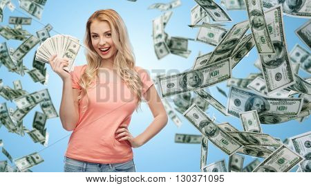 money, finances, investment, saving and people concept - happy young woman with dollar cash over money rain and blue background