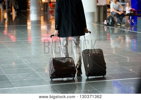 A man with two hand baggage suitcases on a airport