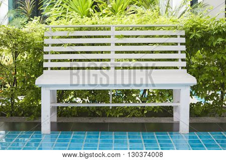 White bench on tile floor with green garden background