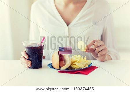 american independence day, celebration, patriotism and holidays concept - close up of woman eating potato chips with hot dog and cola in plastic cup on 4th july at home party