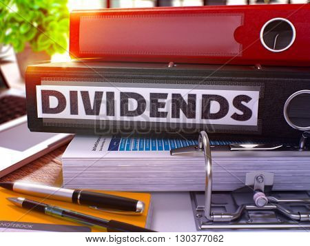 Black Ring Binder with Inscription Dividends on Background of Working Table with Office Supplies and Laptop. Dividends Business Concept on Blurred Background. 3D Render.
