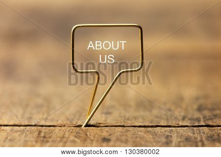 About Us in a golden speech bubble. Speech bubble made of gold wire on rustic grunge wood. Shallow depth of field.