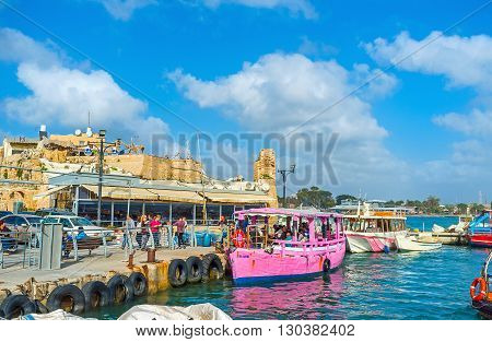 ACRE ISRAEL - FEBRUARY 20 2016: The pink pleasure boat waits the tourists to make a trip along the beautiful coast of old Akko on February 20 in Acre.