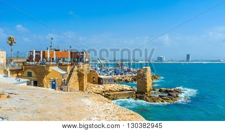 ACRE ISRAEL - FEBRUARY 20 2016: The medieval Crusader harbor with the picturesque ruins is the best place for the tourist restaurants fish taverns and bars on February 20 in Acre.