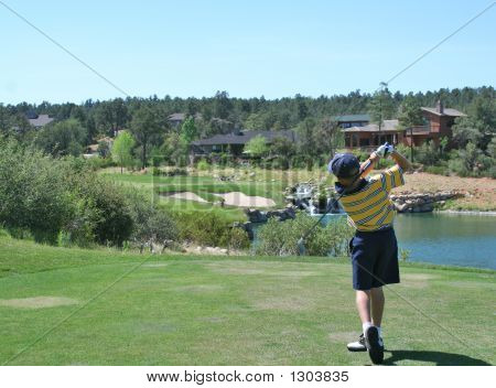 Young Golfer Hitting A Shot Over A Water Hazard