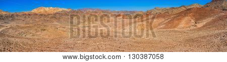 The red valley in Eilat mountains egion with the bright yellow peak on the background Israel.