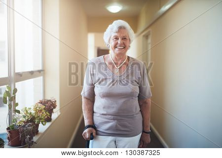 Happy senior woman witPortrait of happy senior woman with walking stick standing at home. Caucasian female looking at camera and smiling.h walking stick standing at home
