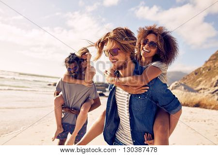 Two happy young men giving their girlfriends piggyback rides. Group of young people enjoying themselves during summertime at the beach.