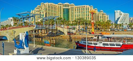 EILAT ISRAEL - FEBRUARY 23 2016: The entrance to the Marina with the Memorial drawbridge and Hilton Hotel Complex on the background on February 23 in Eilat.