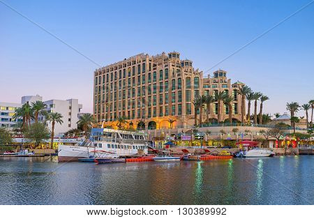 EILAT ISRAEL - FEBRUARY 23 2016: The nice view from marina promenade on the moored boats and the luxury hotel on February 23 in Eilat.