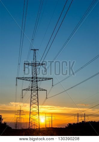 electric pylon with power line at sunset.